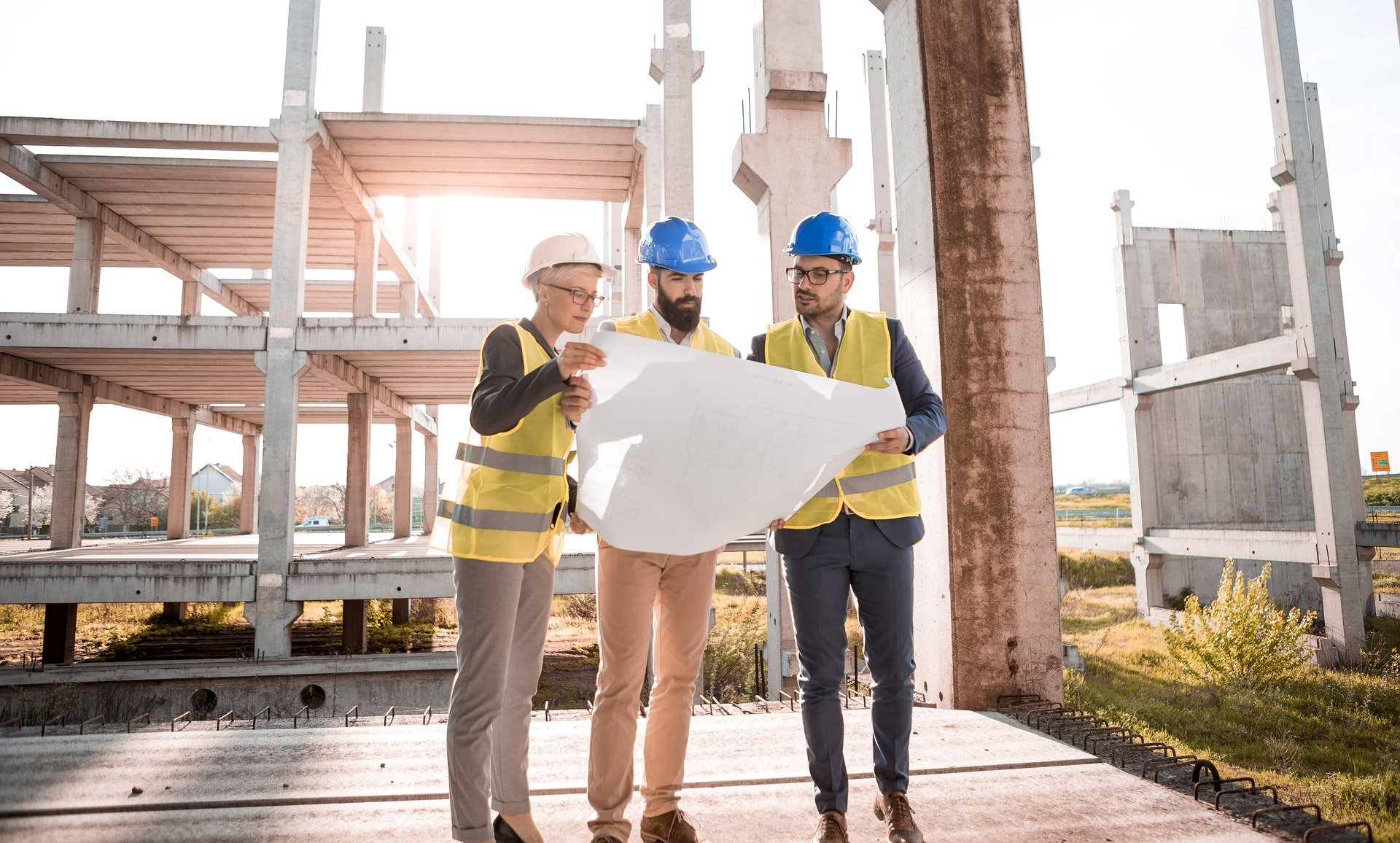 Engineers inspect a building plan in front of a construction site